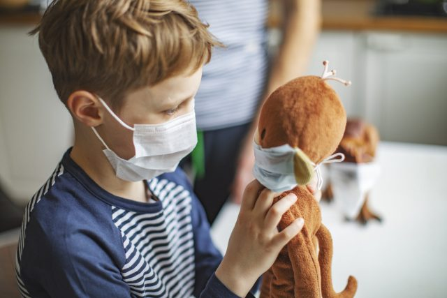 child in face mask with teddy bear